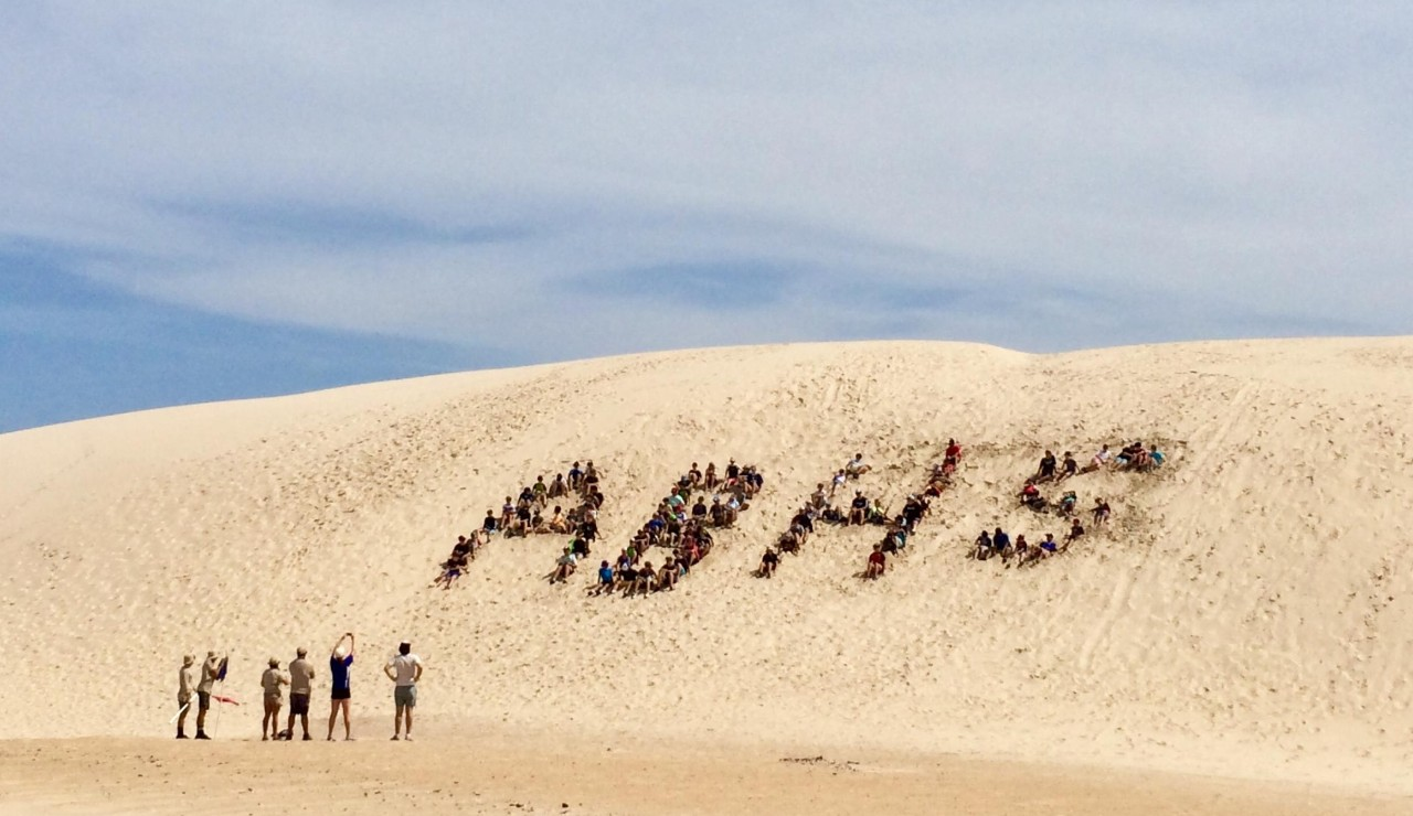 ABHS letters created by boys on sand dune